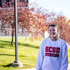 Leah Uselmann smiles for a candid photo outside of Halenbeck Hall at St. Cloud State Minn. (Photo/Chelsea Bauman)