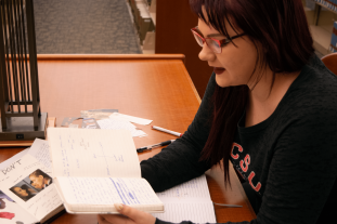 SCSU student Lauen Horan reads aloud from her poetry journal in the Miller Center Library at St. Cloud State University. (Photo/Tyler Gastecki)