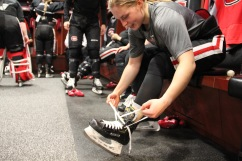 Suvi Ollikainen ties her skates in the women's hockey locker room in St. Cloud, Minn., Saturday, Nov. 17, 2018. (Photo/Janine Alder)