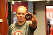 Suvi Ollikainen shows the puck of her first goal in the women's hockey locker room in St. Cloud, Minn., Saturday, Nov. 17, 2018. (Photo/Janine Alder)