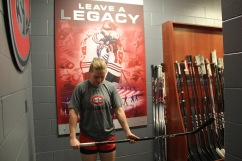 """Suvi Ollikainen poses in front of the """"Leave a Legacy"""" picture in the women's hockey locker room in St. Cloud, Minn., Saturday, Nov. 17, 2018. (Photo/Janine Alder)"""